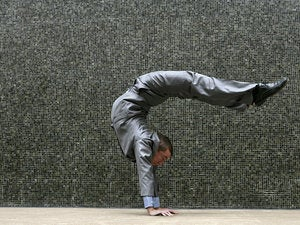 Young businessman doing flexible handstand outdoors twist contort stretch