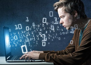 Young man at computer with binary code