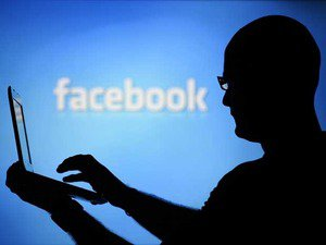 A man is silhouetted against a video screen with a Facebook logo