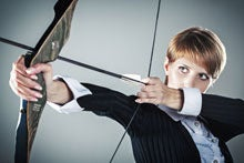 Female executive shooting bow and arrow against green background