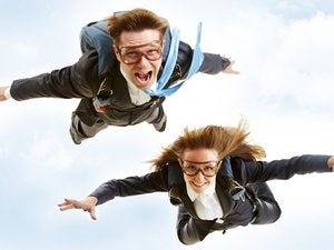 Male and female executives skydiving